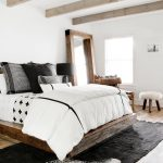 Bedroom, Wooden Floor, Wooden Bed Frame, White Wall, Wooden Framed Mirror, White Bed, Wooden Chairs, Wooden Stool, Black Rug, Wooden Beams On The Ceiling
