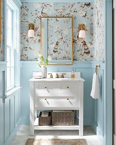 bird wallpaper corner, blue wainscoting wall, white wooden vanity, white floor tiles, golden framed mirror, sconces