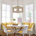 Dining Nook, Wooden Floor, White Wall, Large Glass Window Bay, White Wooden Bench, Yellos Cushion, Yellow Pillows, White Round Dining Table, White Modern Chairs With Yellow Cushion
