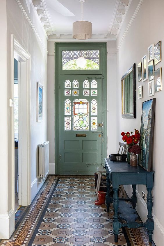 entrance foyer, brown orange pattern floor tiles, white wall, white ceiling, white pendant, blue wooden console table