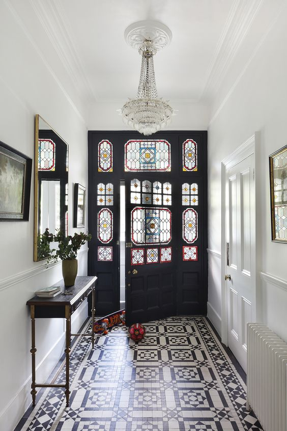 entrance foyer, pattern floor tiles, white wall, crystal pendant, black wooden door with tinted glass