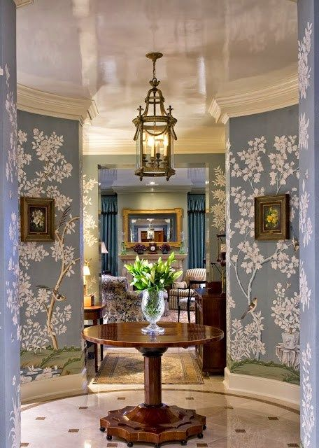 entrance foyer, pattern marble tiles, blue flowery pattern wallpaper, marble ceiling, pendant, round wooden table