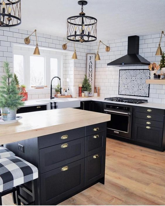 farmhouse kitchen, wooden floor, black bottom cabinet, white top, white subway wall tiles, golden sconces, black cage pendants, black island, wooden top