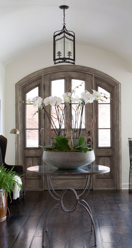 foyer, arch ceiling, natural wood door, round table, wooden floor, chair, flower