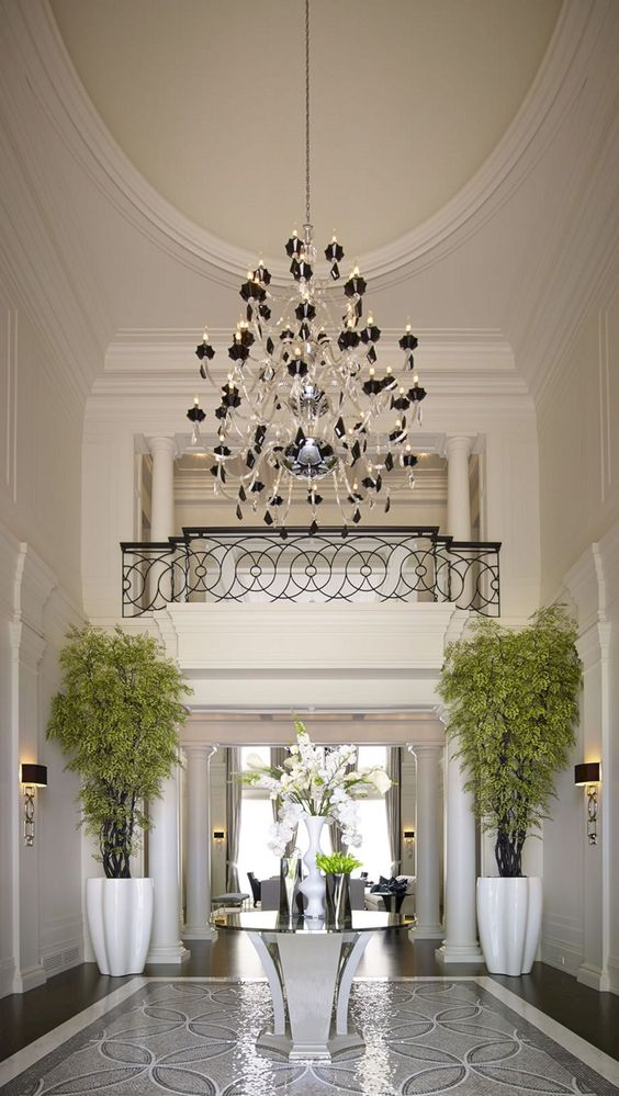 foyer, black floor, round table with glass top in the middle, crystal chandelier, white wall, plants in white tall vase, fence