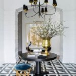 Foyer, White Wall, Black Covered Chandelier, Black Round Table In The Middle, Blue Low Stool, White Black Patterned Floor, Golden Vase