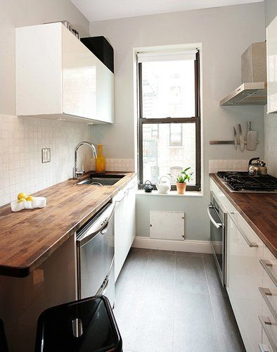 galley kitchen, grey floor, white wall, white cabinet, dark wood kitchenette, window