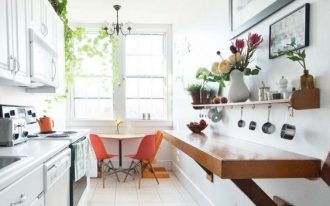 galley kitchen, white floor, white wall, white cabinet, wooden open shelves, orange chairs,