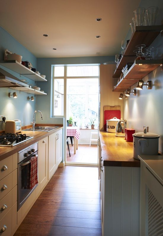 galley kitchen, wooden floor, blue wall, open shelves, white wooden bottom cabinet, wooden top, dining room at the far end