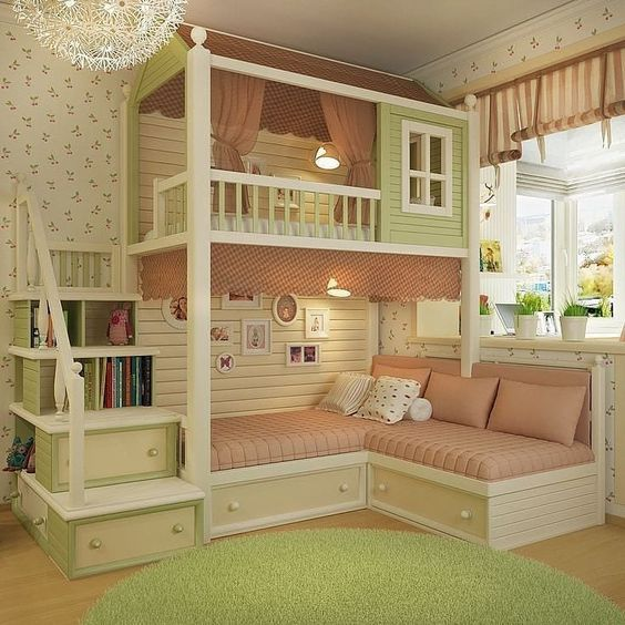 green wooden bunk bed, corner bed at the bottom with pink cushion, green wooden mini house at the top, stairs with shelves and drawers.