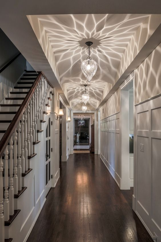 hallway, dark wooden floor, white wall, white pendants with patterned shadow