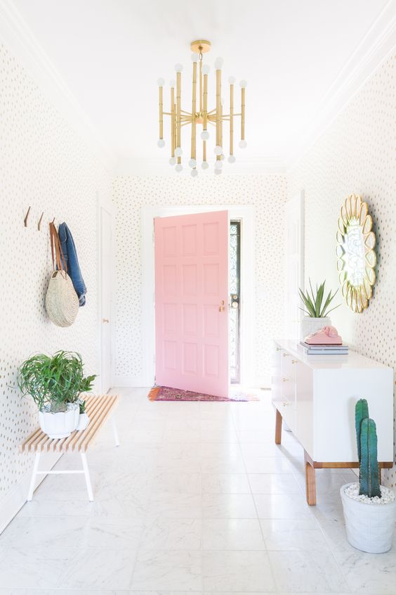 hallway, white floor, white wall with dots, pink door, white cabinet, golden mirror, golden pendant, wooden bench