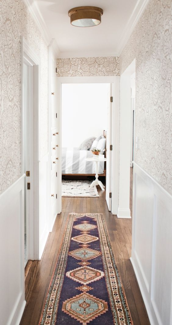 hallway, wooden floor, patterned long rug, white wainscoting, white wallpaper, ceiling lamp