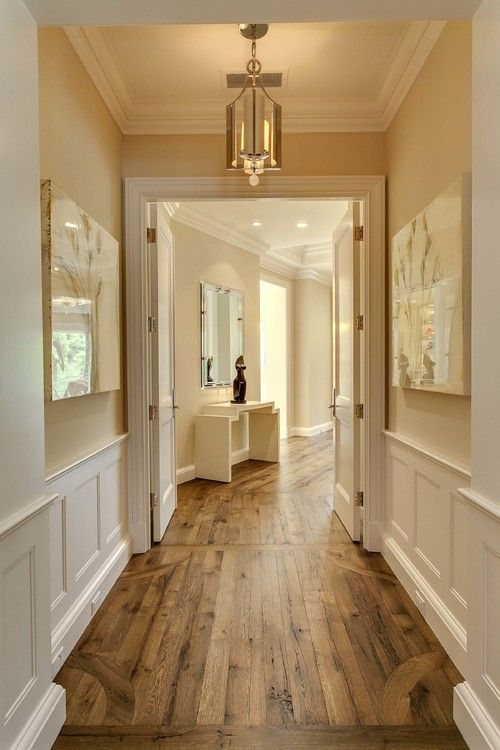 hallway, wooden floor, white wainscoting, cream wall, pendant, white wooden door
