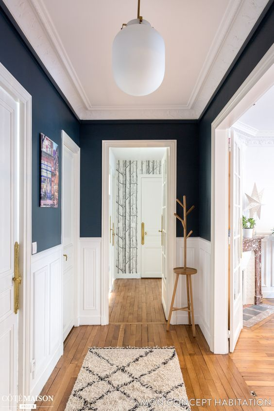 hallway, wooden floor, white wainscoting, dark blue wall, white ceiling, white door, white pendant