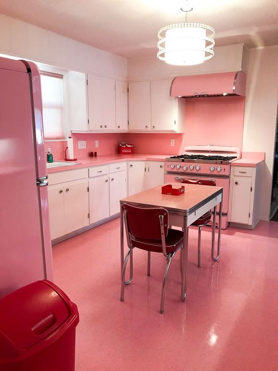 kitchen, pink floor, pink backsplash wall, white cabinet, pink fridge, pink dining table, red chair