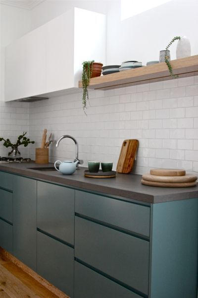 kitchen, white subway baksplash, white wall, deep green modern cabinet. floating shelves