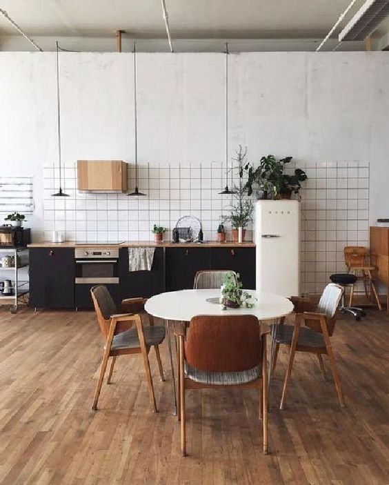 kitchen, wooden floor, white round dining table, wooden chairs, white wall, black cabinet with wooden top, white ridge, black pendants