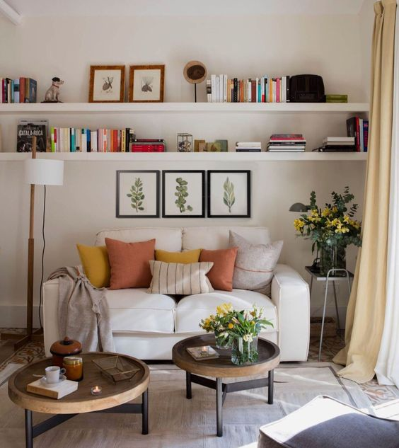 living room, brown rug, white sofa, white floating shelves, white floor lamp, two wooden tray coffee tables, ottoman