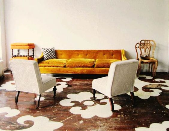 living room, stenciled floor, beige wall, beige chairs, mustard velvet sofa