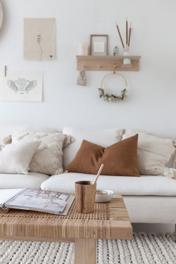 living room, white sofa, white wall, white floor, wooden rattan coffee table, floating shelves,