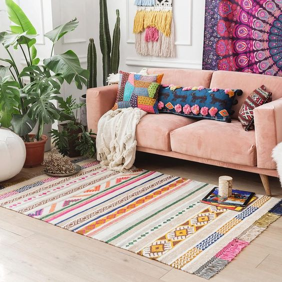 living room, wooden floor, pink sofa, white wall, colorful striped rug