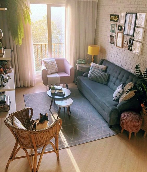 living room, wooden floor, white open wall, blue sofa, pink chair, ratan chair, pink ottoman, blue rug, floating shelves