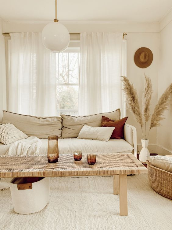 living room, wooden floor, white rug, white sofa, wooden rattan coffee table, rattan basket, white bulubd pendant