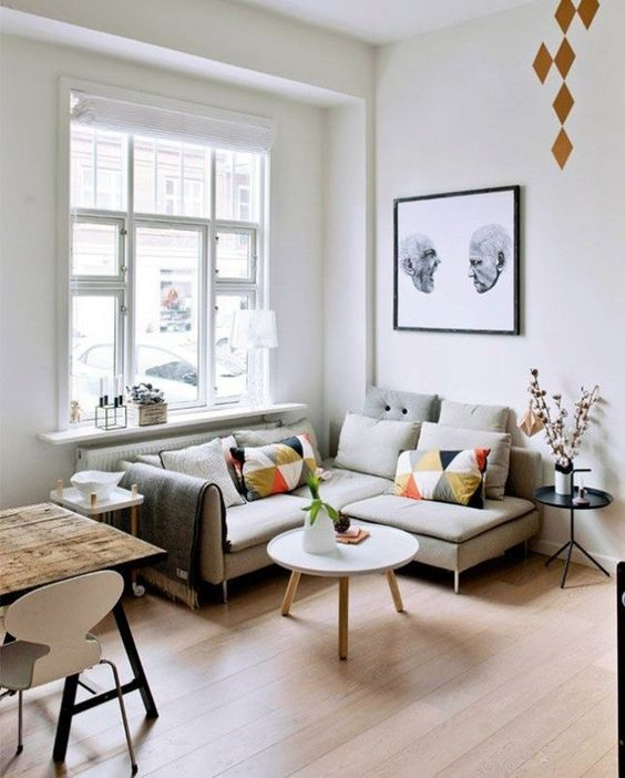 living room, wooden floor, white wall, small corner grey sofa, white coffee table, white floating window rac, black side table