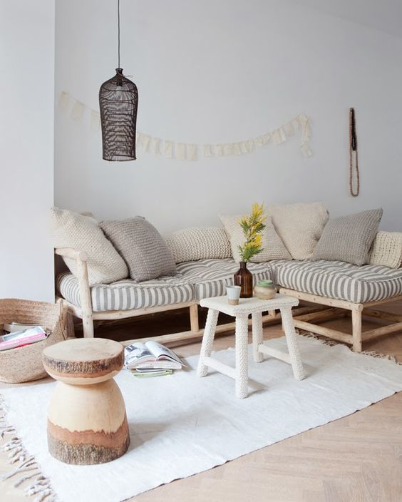 living room, wooden floor, white wall, wooden sofa, striped cushion, white rattan coffee table, black rattan pendant