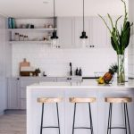 Open Kitchen, White Subway Backsplash Tiles, White Cabinet, White Top Kitchen Island, Glass Pendants, Golden Stool
