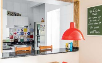 open kitchen, white wall, colorful backsplash, black top kitchenette, black top island, orange pendant, wooden table, orange chairs