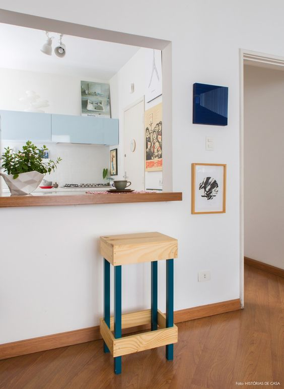 open kitchen,white wall, light blue upper cabinet, wooden top island partition, wooden chair, wooden floor