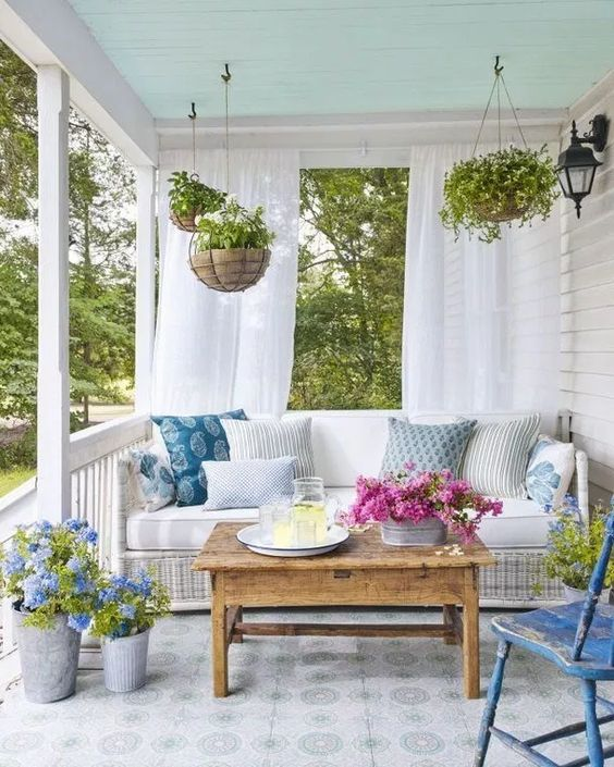 porch, white patterned flor tiles, white plank wall, white rattan bench, wooden coffee table, blue wooden chair, hanging plants on pots, curtain
