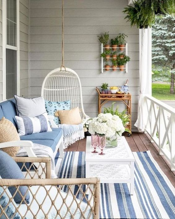 porch, wooden floor, white coffee table, grey plank wall, white rattan swing, white wooden bench, rattan chair, white wooden fence