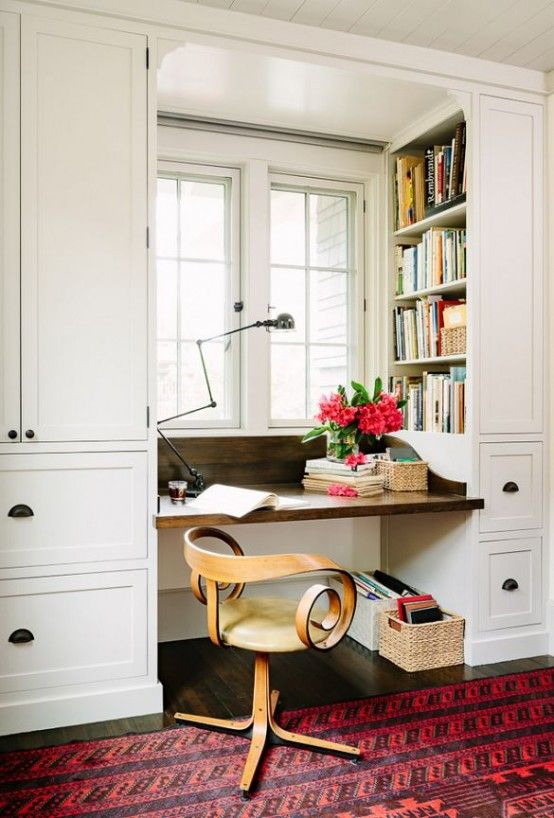 small study, wooden floor, pink rug, white cupboard, shelves, built in table in between, wooden chair