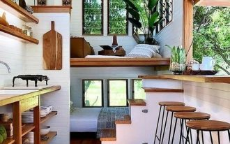 tiny house, wooden floor, white wooden plank wall, bed on the back with low ceiling, living room above, low stairs, kitchen, floating dining table with large glass window
