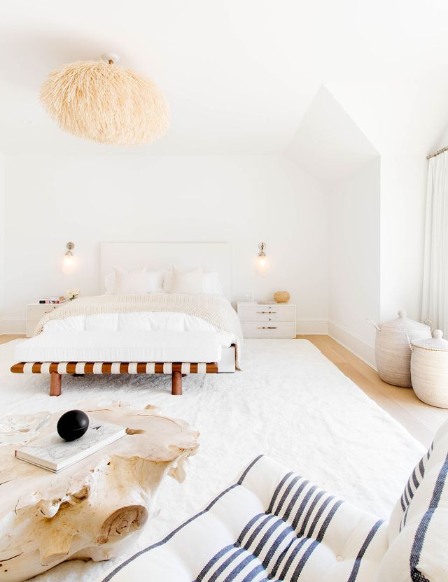 white bedroom under the arch ceiling, wooden floor, white rug, white linen, wooden bench with white cuhion, white blue soa, wooden slab coffee table