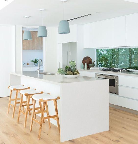 white kitchen, white wall, white island, wooden shite stool, pale blue pendant, silver top