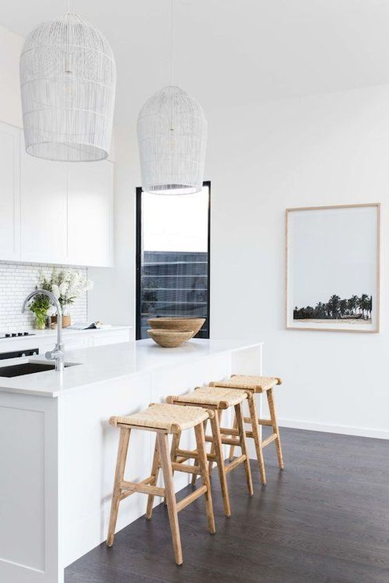 white rattan pendant, white island, wooden floor, wooden rattan stool, white wall, white subway backsplash tiles