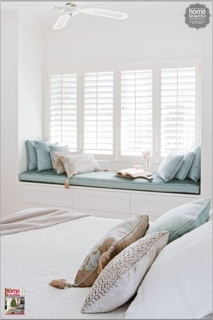 window nook, white built in bench, blue cushion and pillows, white ceiling fan