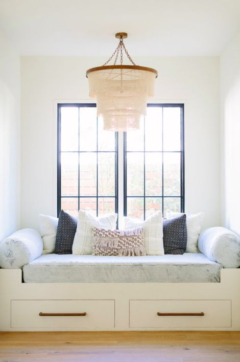 window seat, white bench with drawers, light grey cushion, pillows, chandelier, white window