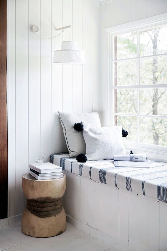 window seat, white wooden floor, white wooden bench, white wooden wall, white blue striped cushion, white sconce