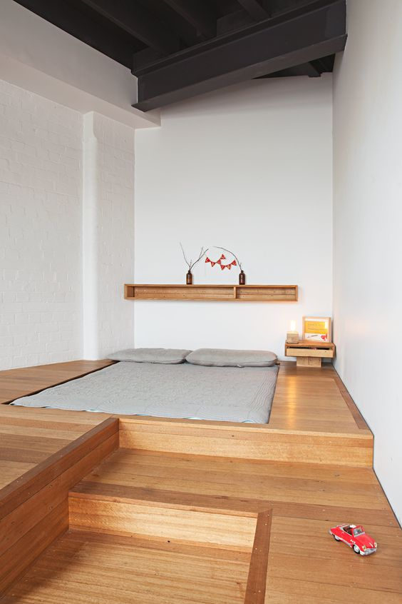 wooden bed platform, bed on the floor nook, white wall