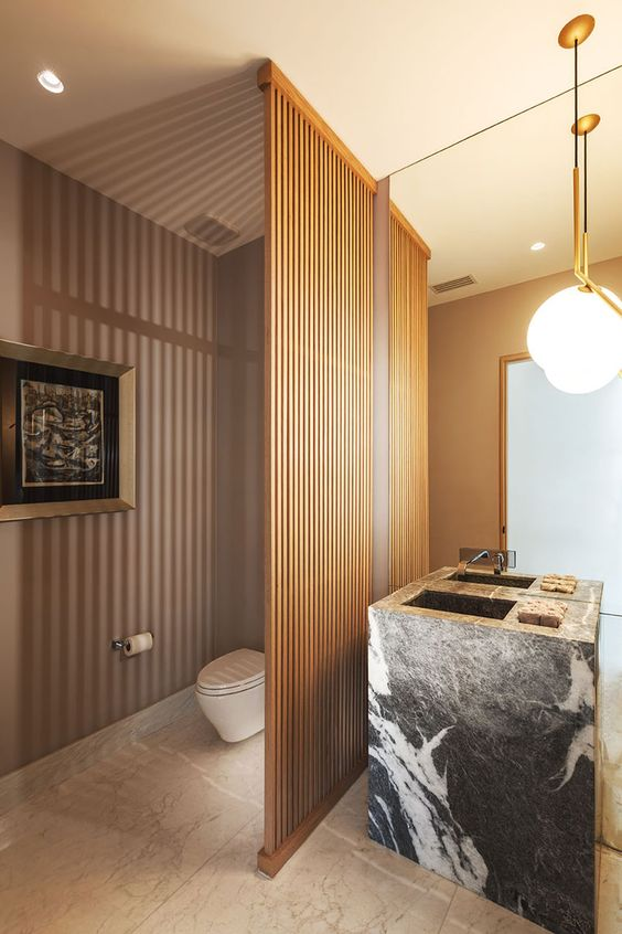 wooden grid partition in the bathroom, marbled floor tiles, dark grey marble sink, large mirror, white bulb pendants