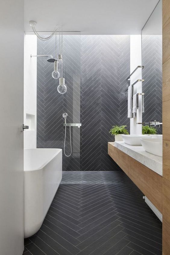 bathroom, black herringbone floor and accent wall, white wall, white tub, floating vanity, glass bulb pendant, white top, white sink
