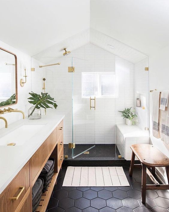 bathroom, black hexagonal floor tiles, white subway wall, wooden cabinet with white top, golden framed mirror, black floor shower, wooden bench