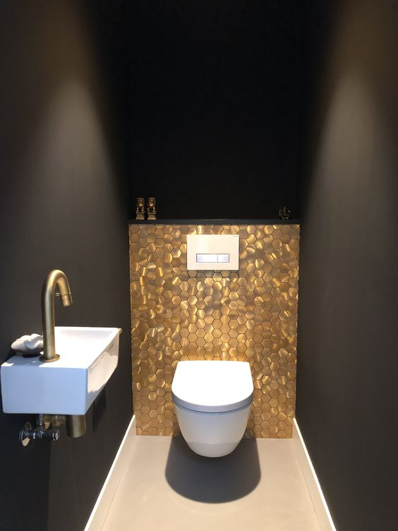 bathroom, black wall, white sink, golden faucet, white toilet, brown floor, golden hexagonal tiles on the accent wall