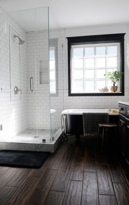 bathroom, black wood floor tiles, white subway wall, black tub, shower area, dark cabinet, white top