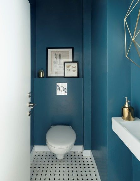 bathroom, blue wall, white black polka dot floor tiles, white floating shelves, whtie toilet